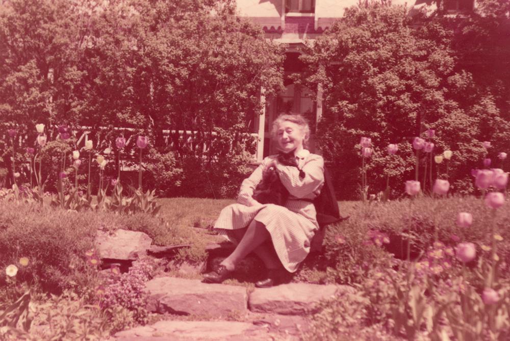 Photo couleur. Femme âgée assise au milieu de son jardin fleuri.