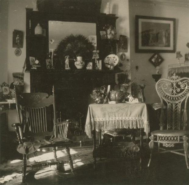 Black-and-white photograph of a drawing room. Two chairs and a table in the foreground are in front of a fireplace with a large mirror over it. There are numerous pictures and decorative objects on the wall and the mantelpiece.
