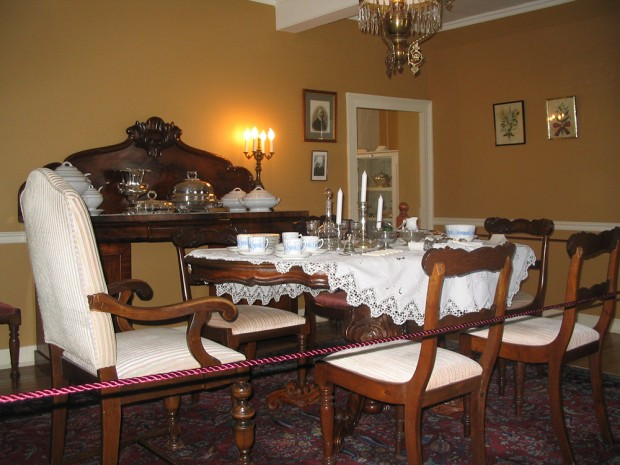 Colour photograph of a table with porcelain dishware and silverware. An imposing sideboard is in the background.