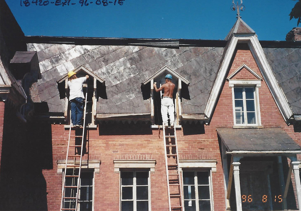 Colour photograph of workers on ladders repairing the dormer windows of Manoir Fraser.