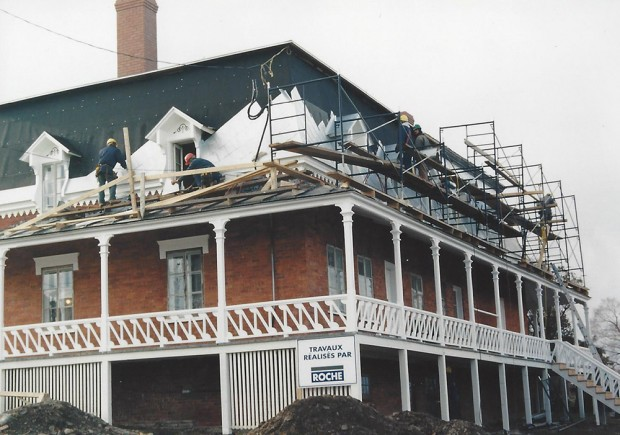 Colour photograph of workers applying a new covering to the mansard roof.