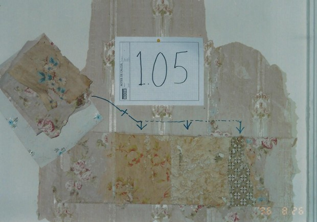 Colour close-up photograph of part of a wall, showing the different wallpaper that covered it over the years.