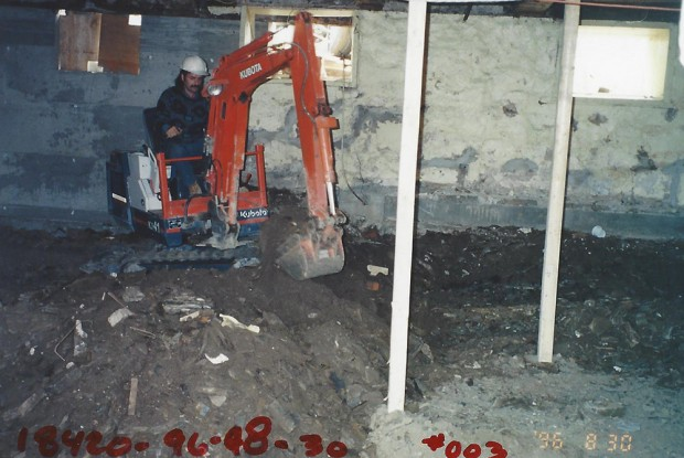 Colour photograph of a worker excavating the basement of Manoir Fraser with a mechanical shovel.