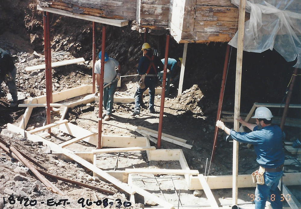 Colour photograph of workers preparing the formwork to cast the new foundations of the Manoir.