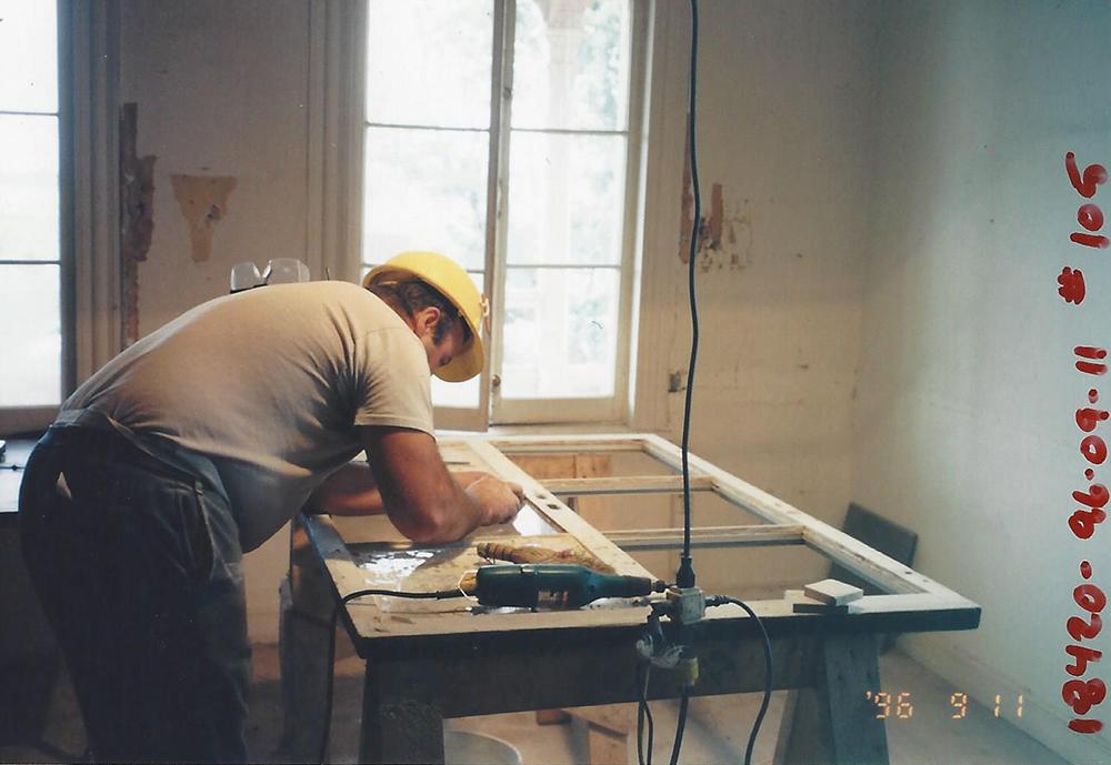 Photo couleur. Un homme restaure une fenêtre à l'intérieur du manoir.