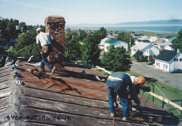 Colour photograph of workers repairing the roof. Houses and the river can be seen in the background.