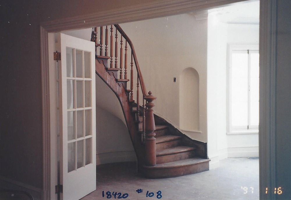 Colour photograph of the empty entrance hall of Manoir Fraser with a wooden staircase in the centre.