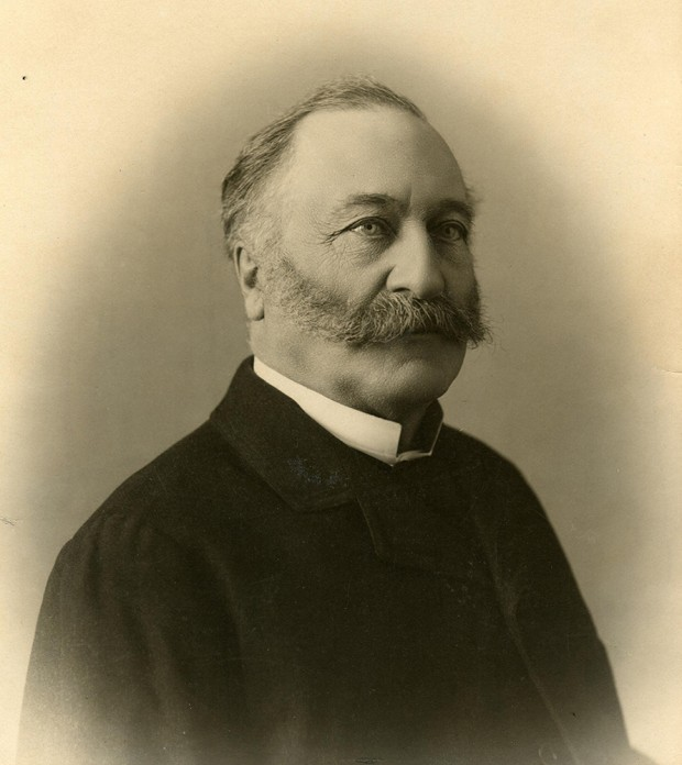Black-and-white head-and-shoulders photograph of a man with a huge moustache and greying hair, dressed in a black suit.