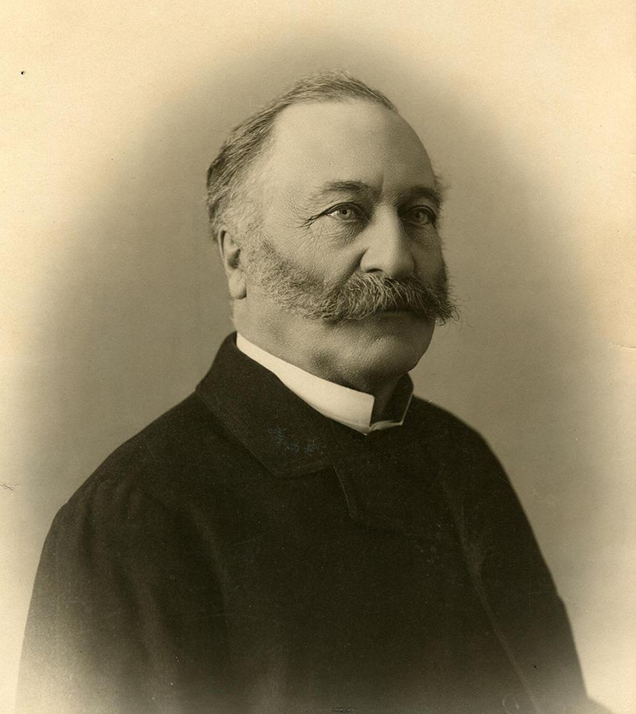 Photo noir et blanc. Portrait d'un homme moustachu aux cheveux grisonnants portant un veston noir.