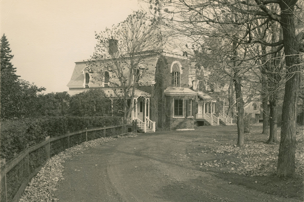 Black-and-white photograph. A road in the foreground leads to a house surrounded by trees.