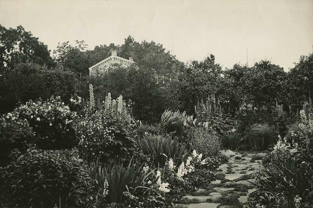 Black-and-white photograph of a lush flowering garden with a flagstone walkway in the foreground. Many mature trees hide the house in the background.