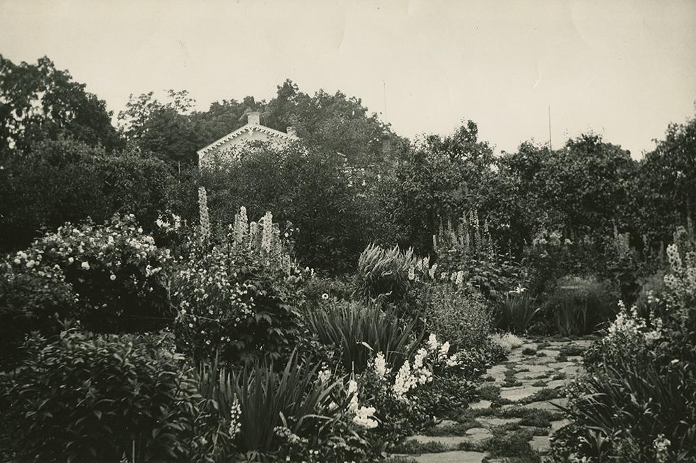 Photo noir et blanc. Jardin abondamment fleuri avec allée de pierre à l'avant-plan. De nombreux arbres matures cachent une maison à l'arrière-plan.