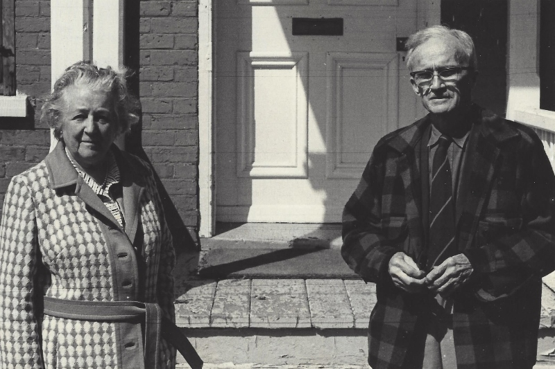 Black-and-white photograph of a man and a woman standing outside Manoir Fraser.