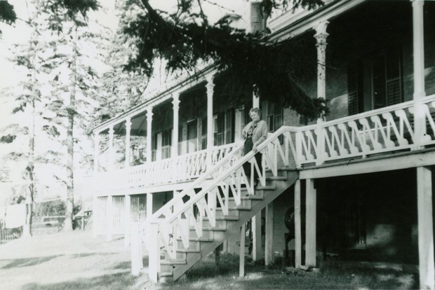 Black-and-white photograph of an elderly woman standing on the staircase leading to the large veranda that wraps around Manoir Fraser.