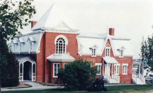Colour photograph. Façade of a brick house in close-up.