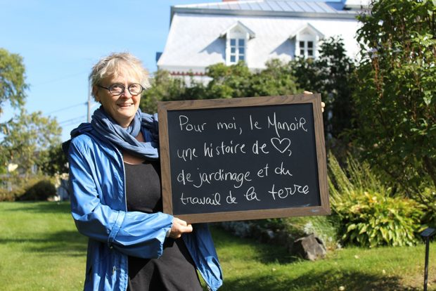 Colour photograph of a woman holding a small backboard with the words To me, the Manoir represents an affair of the heart, a story of gardening and working the soil. A large house with a mansard roof is in the background.