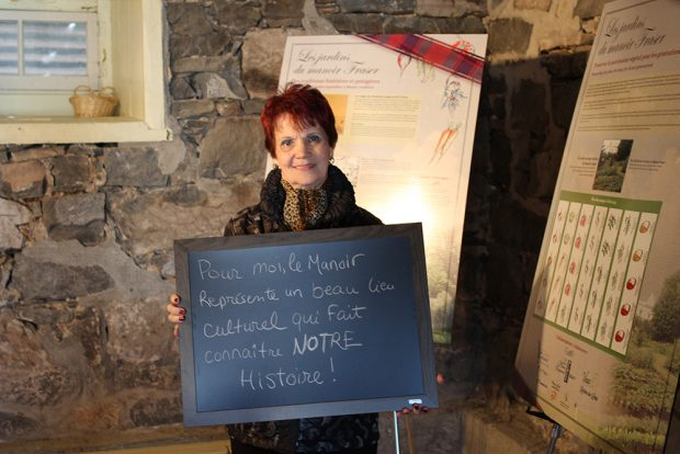 Colour photograph of a woman standing inside the manor holding a small blackboard with the words To me, the Manoir represents a lovely cultural site that promotes knowledge of OUR history.