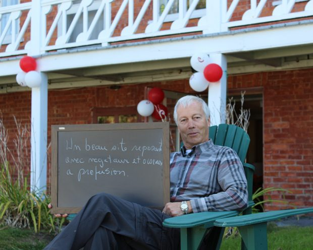 Colour photograph of a man sitting in a garden chair, holding a small blackboard on which he has written what the Manoir represents to him: A lovely, restful place, with a profusion of plants and birds. A red brick house is in the background.