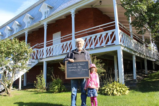 Colour photograph of a man holding a small blackboard with the words: To me, the Manoir represents memories of youth. A little girl stands beside him, and a large brick house with a big veranda is behind him.