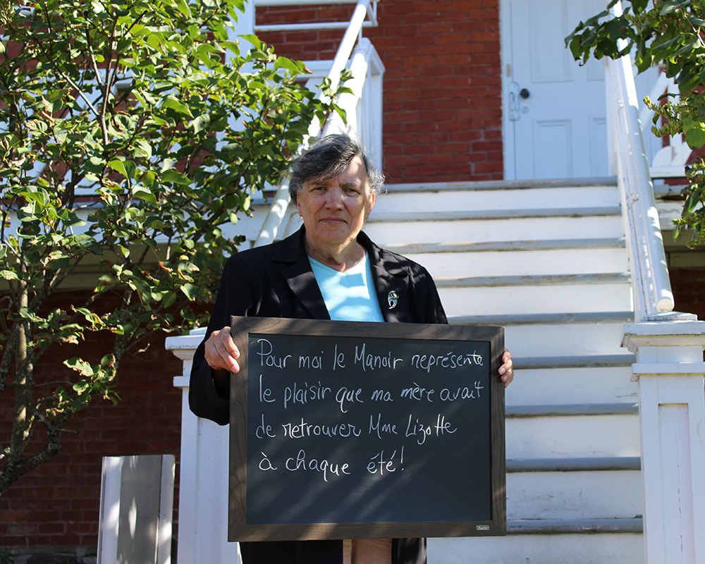 Colour photograph of a woman holding a small blackboard with the words To me, the Manoir represents the pleasure my mother used to have meeting Madame Lizotte every summer. A stairway leading to a veranda is in the background.