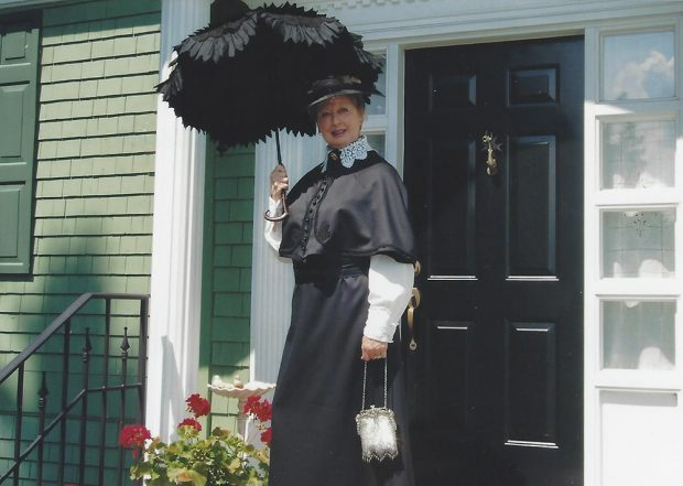 Colour photograph of a woman in a Victorian dress in front of a house painted green.