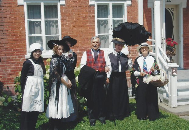 Colour photograph of one man and five women dressed in period costumes, posing for the camera in front of a brick house.