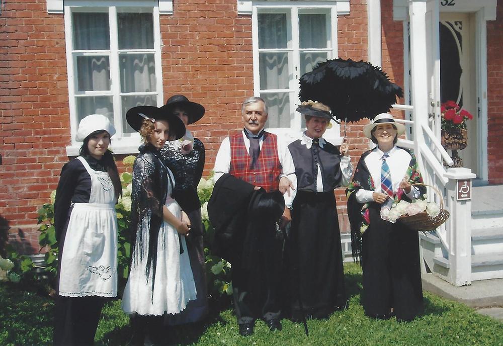 Photo couleur. Six personnes, cinq femmes et un homme, vêtus de costumes d'époque, prennent la pose devant une maison de briques.