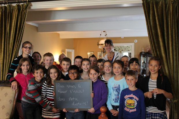 Colour photograph of a group of about 20 smiling schoolchildren standing between the manor drawing room and the dining room. One holds a small blackboard with the words To us, the Manoir is a part of our history.
