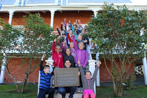 Colour photograph of about 20 smiling schoolchildren with their arms raised, on a staircase leading to a red brick house. Their teacher is holding a small blackboard with the words To us, the Manoir represents a world of stories, treasures, and discoveries!