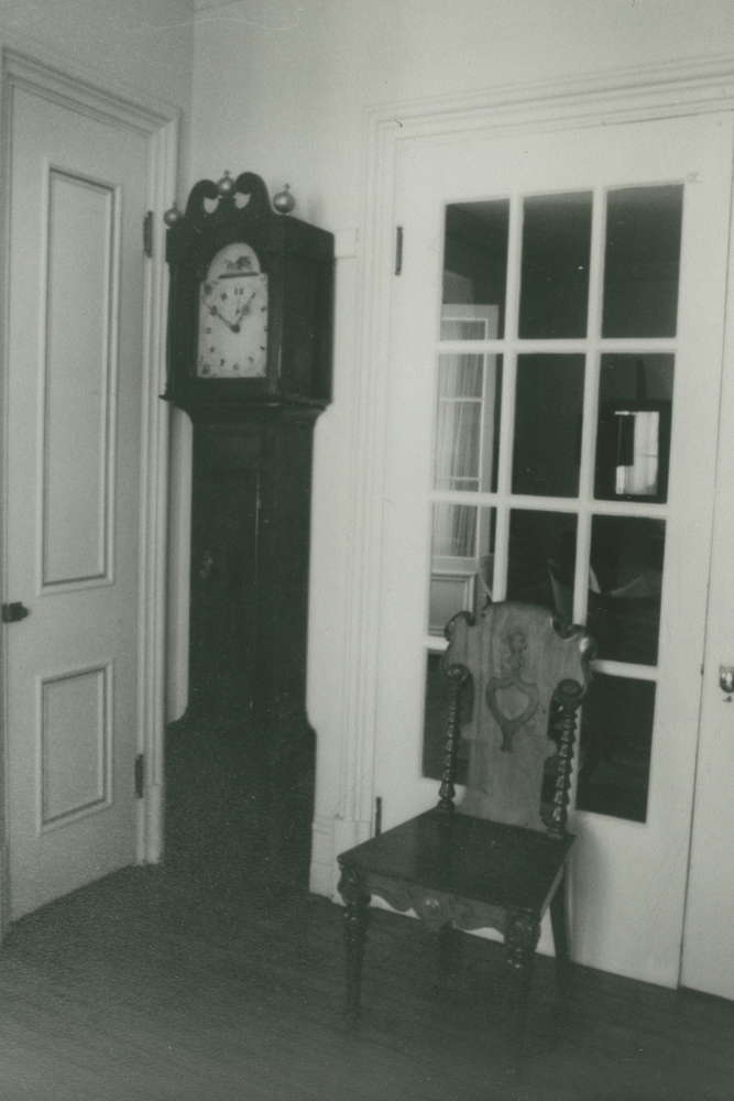 Black-and-white photograph. A grandfather clock stands in a corner. Beside it is a chair, placed against a glass door.