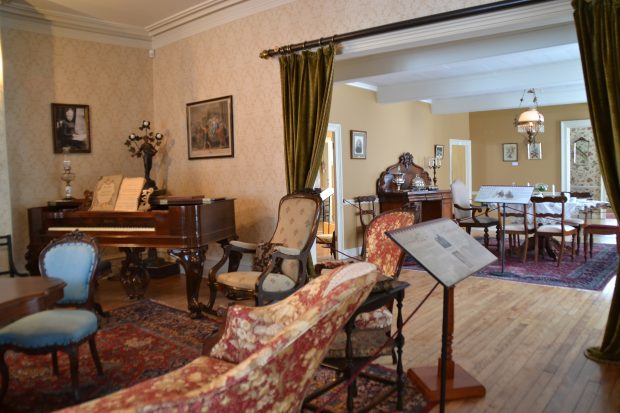 Colour photograph of the drawing room, decorated in the Victorian style. A baby grand piano is in the corner. An opening in the wall gives onto the dining room. An explanatory panel is on a stand on the right.