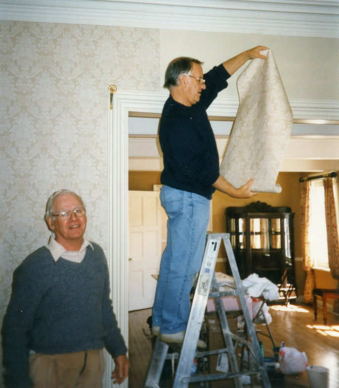 Colour photograph of two men, one on a step-ladder, putting up wallpaper in the drawing room.