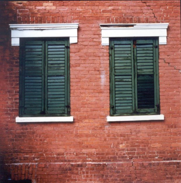 Close-up colour photograpĥ of two windows in a brick house with closed shutters.