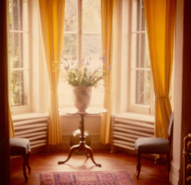 Colour photograph of the entrance hall of Manoir Fraser with a bouquet of flowers in the bay window.