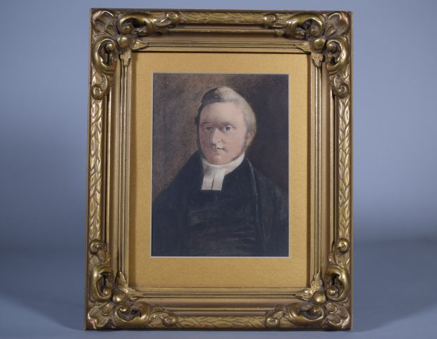Portrait of William Abbott, charcoal, head and shoulders, adult. He has short hair and light brown sideburns, light grey eyes. He is wearing a black minister's robe and a white collar. The background is dark grey-brown. The portrait is set in a gilded woodwork frame with gold mat.