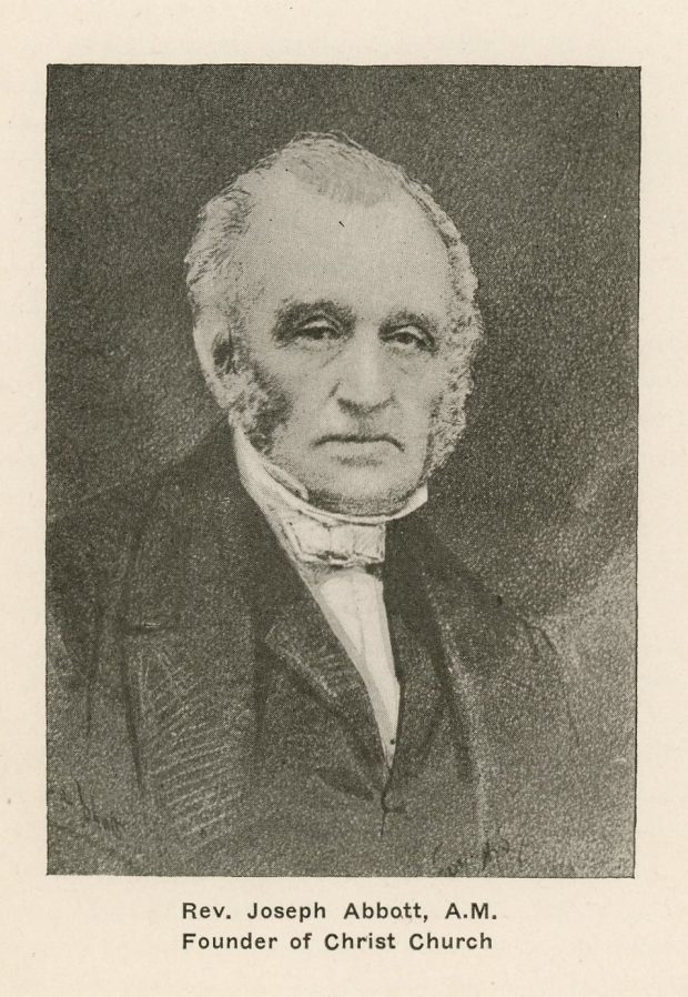 """Black and white portrait of an elderly Reverend Joseph Abbott, head and shoulders. He has short hair and grey and white sideburns, and is looking at the camera with a serious expression. He is wearing a black minister's robe and a white collar. The background is black. The inscription under the portrait reads """"Rev. Joseph Abbott, A.M. Founder of Christ Church""""."""
