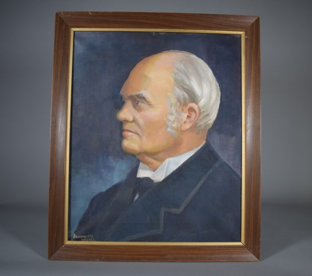"""Profile portrait of an elderly John Joseph Caldwell Abbott, oil, colour, head and shoulders. His hair and sideburns are white and grey. He is wearing a white shirt with black tie and jacket. The background is dark blue-grey. The artist's signature, """"Jeannette Wales"""", can be seen in the lower left corner. The portrait is set in a simple wood frame with a narrow gold mat."""