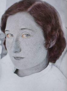 Photographie en noir et blanc avec détails colorés d'une femme adulte, épaules et tête. Elle regarde l'objectif, la tête tournée de trois-quarts. Ses yeux bleu pâle sont rougis et ses cheveux sont rouge-roux. Elle a les lèvres et les sourcils fins et des taches de rousseur sur les joues et le nez. Elle porte un chandail blanc, le col arrêtant au milieu du cou.