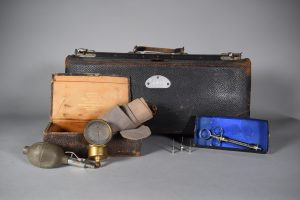 Colour photograph of a doctor's bag and instruments. At the back there is a large rectangular black leather bag with a handle in the centre and clasps on both sides. The bag is slightly damaged at the corners. In front of the bag and to the left is a smaller case, also made of black leather. It is open, showing a beige interior. The case contains a large beige-grey cotton bandage. A blood pressure bulb and a gold-coloured sphygmomanometer lean against the case. To the right, there is an old syringe in a cardboard box and three needles can be seen to its left.