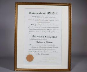 Diplôme de l'Université McGill. « Doctorem in Medicina » décerné à « Maud Elizabeth Seymour Abbott » par l'Université McGill. Le texte sur le diplôme est en latin. Dans le coin inférieur gauche, le sceau rouge de l'Université McGill, à sa droite, de nombreuses signatures. Le diplôme est dans un mince cadre doré et simplement orné et un passepartout blanc.
