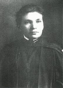 Face recto d'une carte postale noire et blanche d'un portrait de Maude Abbott, jeune adulte, de la taille à la tête. Elle porte un habit et une toge de graduation foncés. Ses cheveux foncés sont attachés à l'arrière de sa tête et sa tête est légèrement tournée vers la gauche.
