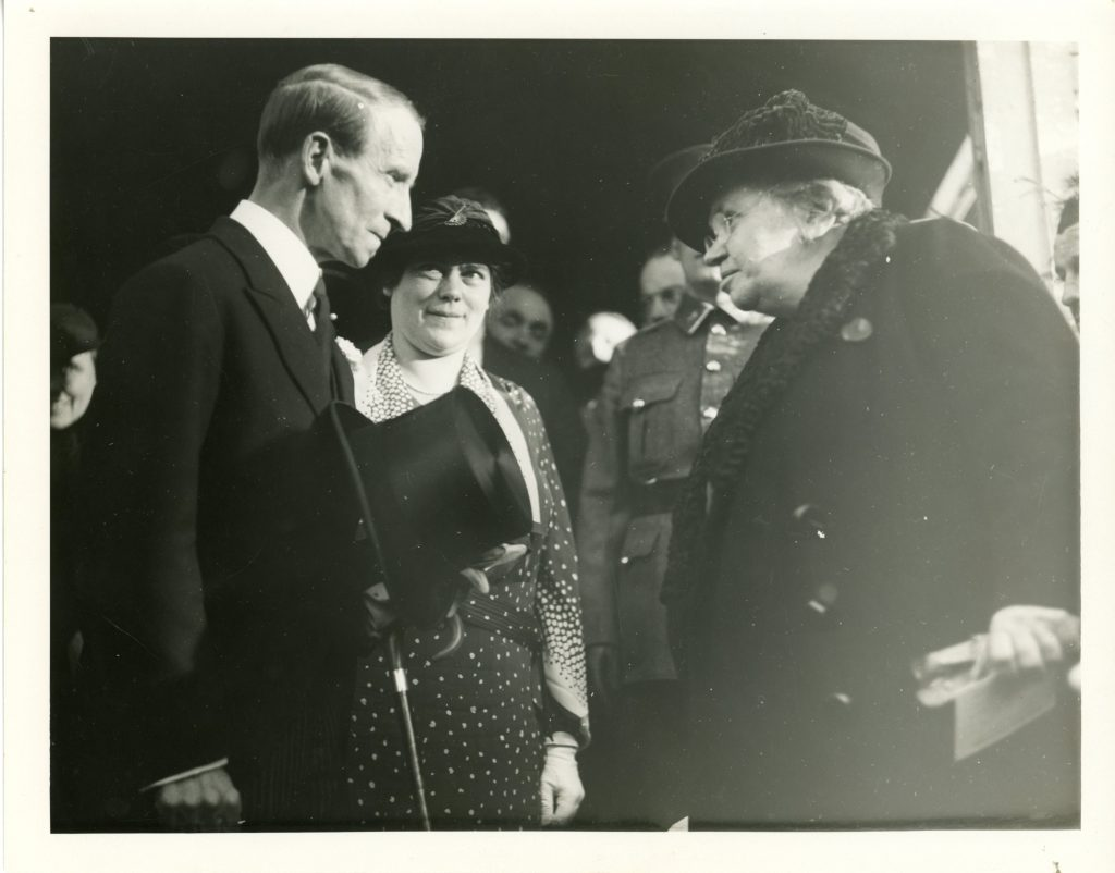Black and white photograph of Maude Abbott and Lord Tweedsmuir during the Sir John Joseph Caldwell Abbott memorial dedication ceremony in 1936. Lord Tweedsmuir, on the left, is seen in profile. He has short hair, parted on the side, and is wearing a black jacket. He is exchanging glances with Maude Abbott, on the right in the photo. She is elderly and is wearing a black coat with a fur collar. Behind Lord Tweedsmuir, a woman in a dark dress with white polka dots and a stylish hat is looking at him attentively. The crowd can be seen behind them.