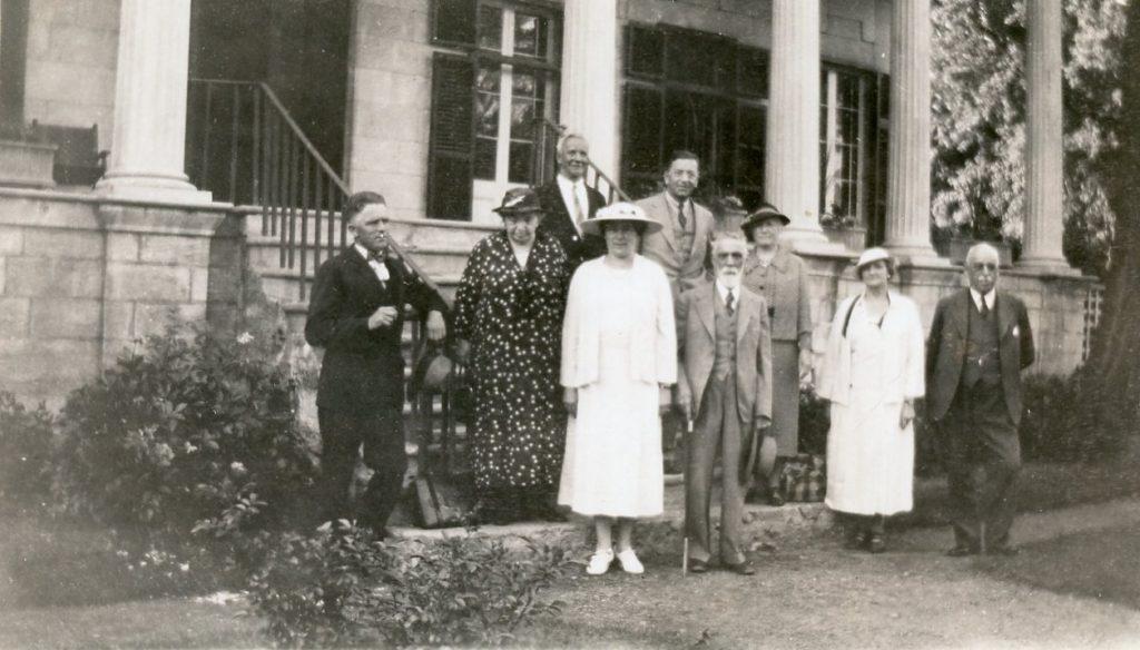 Photographie en noir et blanc des neuf membres fondateurs de la Société historique du comté d'Argenteuil. Ils sont debout devant et dans les escaliers d'une grande maison en pierre avec colonnes et volets foncés. Maude Abbott est la deuxième à partir de la gauche, portant une robe noire à pois blancs et un chapeau foncé. Les trois autres femmes sont vêtues de robes et chapeaux chics et les cinq hommes portent des complets.