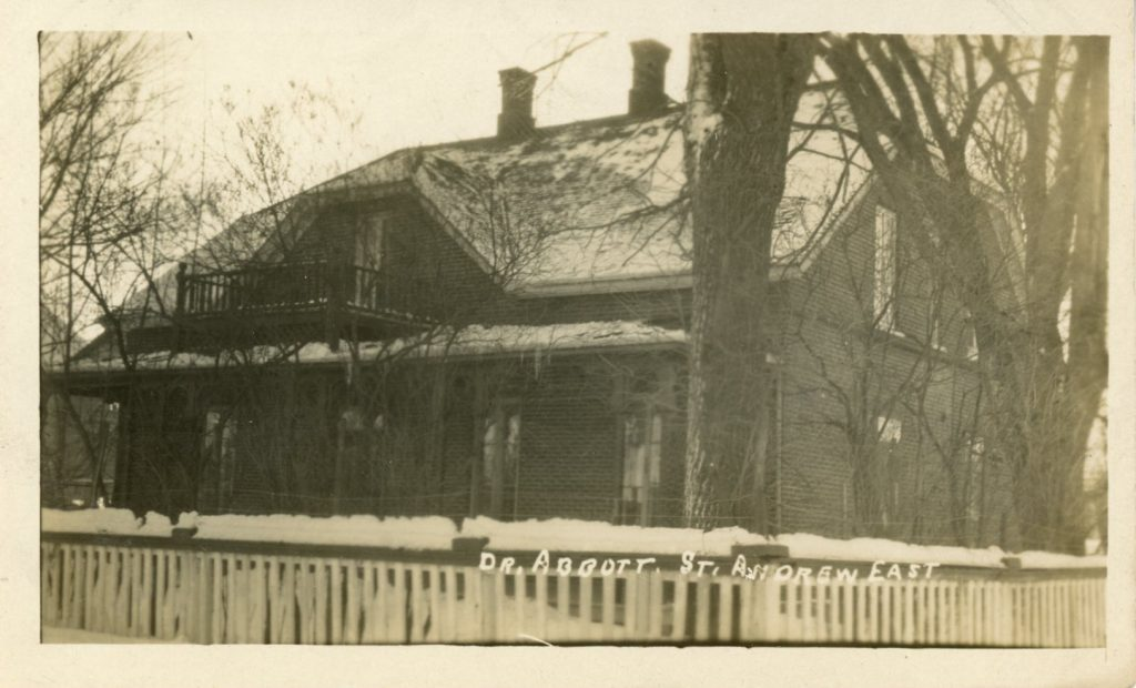 Photograph of Elmbank, Maude Abbott's home, in winter, sepia. It is a two-storey brick house with a gable roof, two chimneys and a gallery on each floor. There is a white wooden fence in front of the house, which is surrounded by leafless trees.