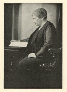 Photographie de Maude Abbott, âgée, noir et blanc. Elle est vue de profil, l'air concentré, lisant un livre à un bureau en bois et assise sur un siège en bois sculpté. Elle porte des vêtements foncés, un collier de perles et ses cheveux sont attachés derrière sa tête.