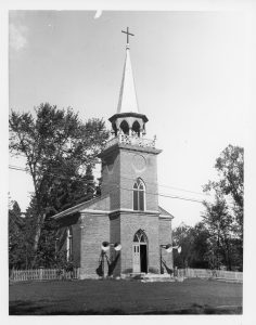 Black and white photo of Christ Church. The church is made of brick, the double door in the centre is open on one side and topped by a lancet window. Another window of the same shape can be found in the bell tower. The openings in the bell tower are lancet-shaped and it is topped by a tall spire crowned with a black cross. Two loudspeakers are mounted on either side of the door and there are many trees behind the church.