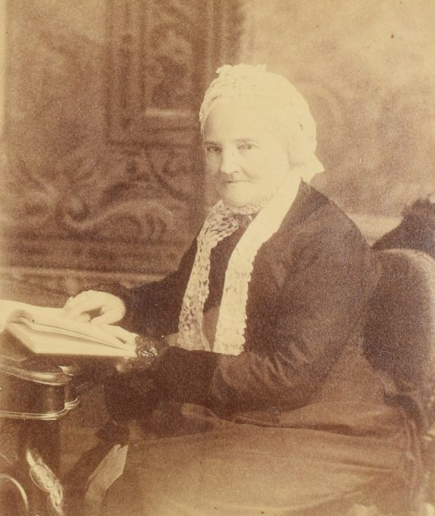 Sepia photograph of an elderly Frances Mary Smith, 1880, sitting, from the knees up. She is facing slightly left and looking at the camera with a calm expression. Her left hand rests on an open book on a desk. She is wearing a black dress and a white lace cap. Her white hair is tied behind her head, under the cap.