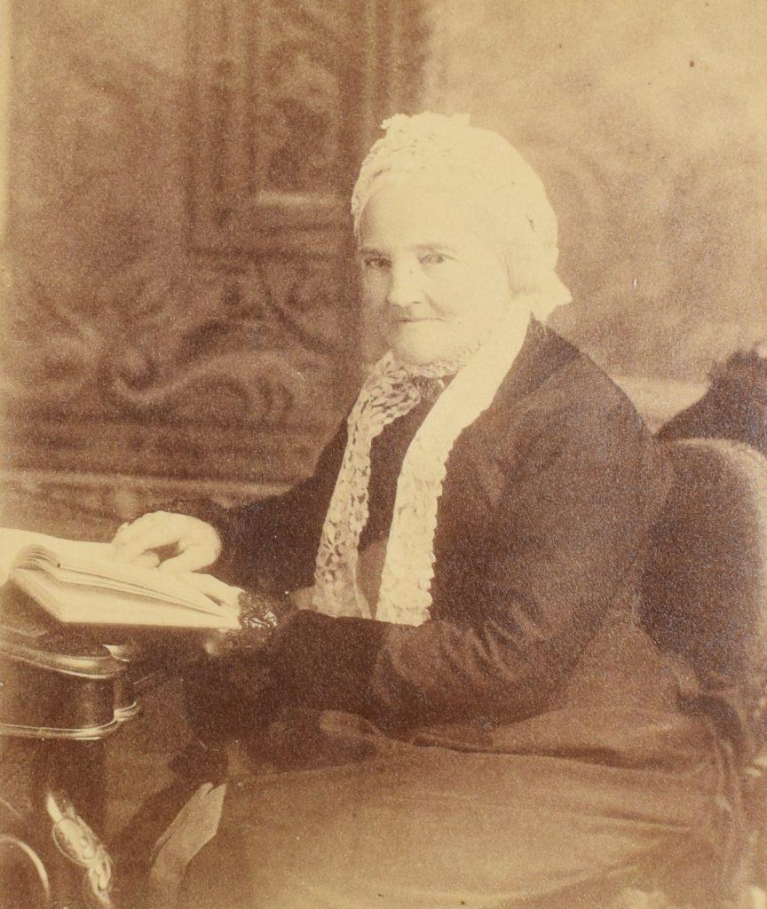 Photographie sépia de Frances Mary Smith âgée, en 1880, assise, des genoux à la tête. Elle regarde l'objectif, la tête légèrement tournée, l'air serein. Elle est appuyée sur un bureau, la main gauche sur un livre ouvert. Elle porte une robe noire et un bonnet en dentelle blanc. Ses cheveux blancs sont attachés à l'arrière de sa tête, sous le bonnet.