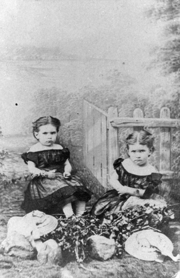 Black and white photograph of Maude and her sister Alice as children. They are sitting by a fence and gazing seriously at the camera. They are wearing dresses with bare shoulders and dark puffy sleeves. Maude, on the left, has dark hair tied behind her head and wears a flower on her right arm. Alice, on the right, has light hair, also tied behind her head. They are sitting behind an arrangement of flowers, two hats and three rocks on the lawn.