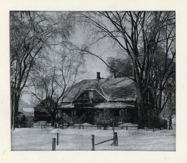 """Photograph of Elmbank, Maude Abbott's home, in winter, black and white. It is a two-storey brick house with a gable roof, two chimneys and a gallery on both floors. There is a wooden fence and a sign marked """"HONEY"""" in front of the house, and many trees on the property."""